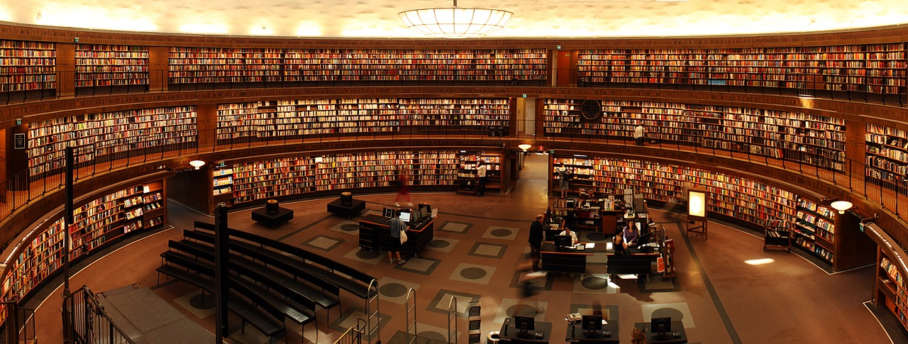 a huge library in oval shaped filled with tons of books in the shelves