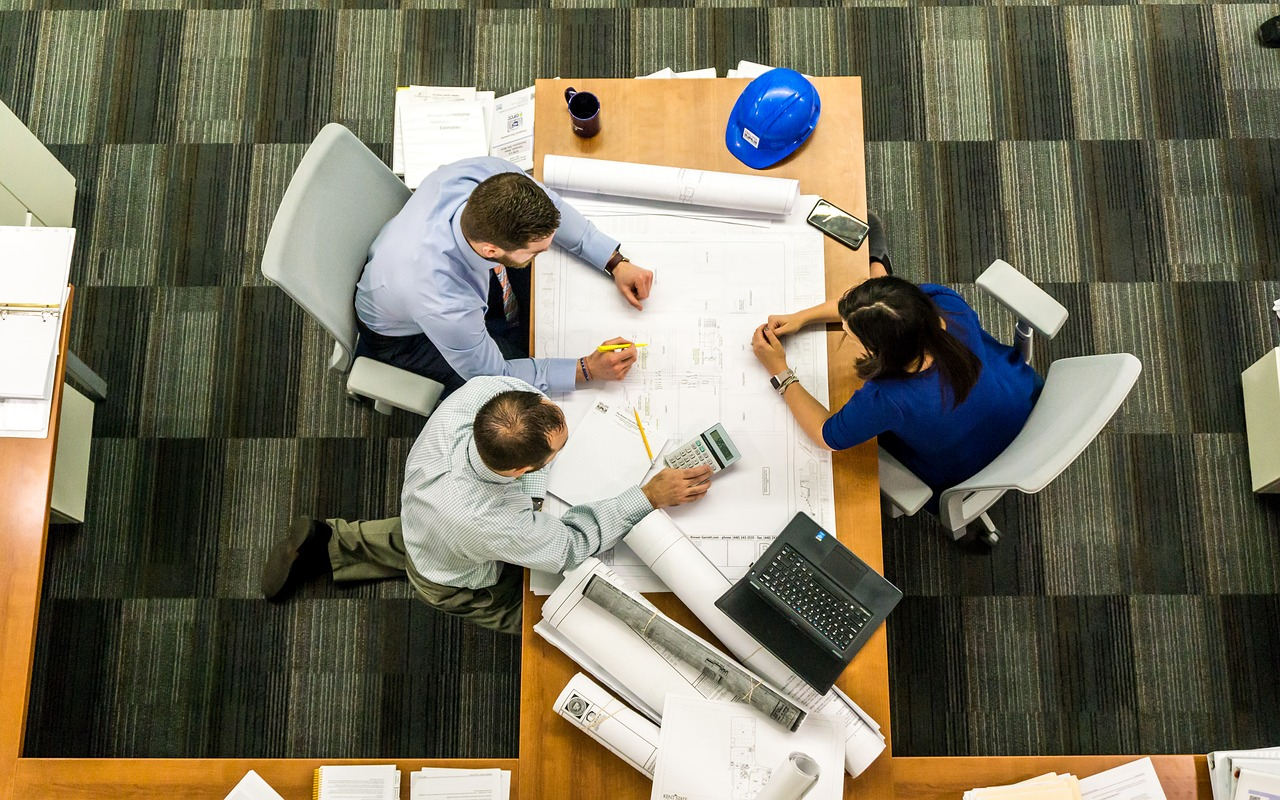 three people on a meeting with a large blueprint on top of their table
