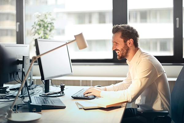man smiling in front of computer